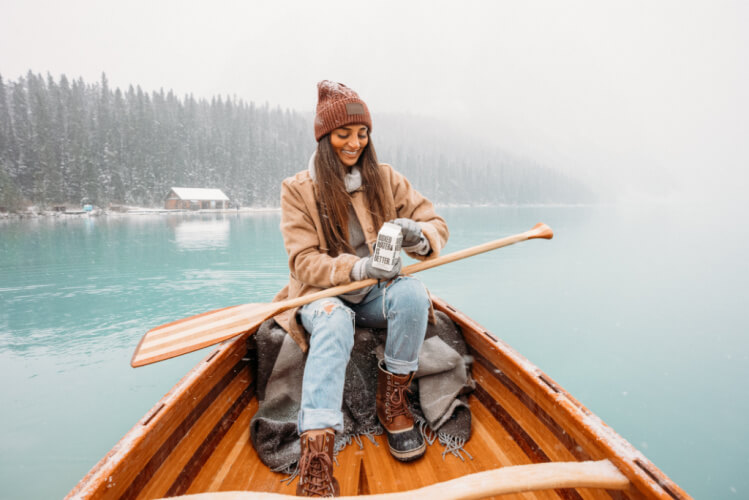 """Text reads: """"Keep heating costs down this winter. femmefrugality.com""""Woman bundled up on a canoe in the middle of winter, opening a box of water."""