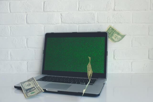 laptop on white table against white brick wall with a close-up of grass as a screensaver. Dollar bills appear to be falling from the sky onto the computer.
