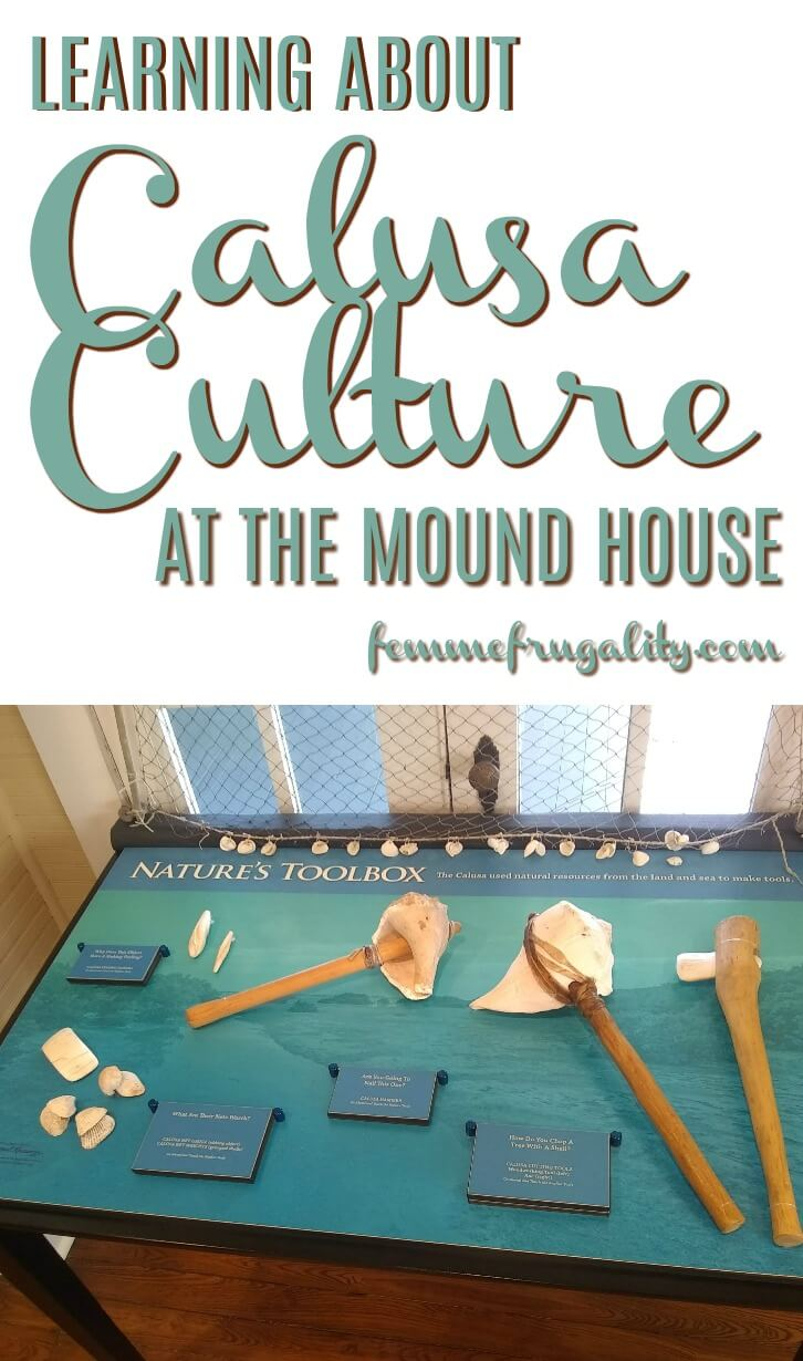"""Blue text with brown drop shadow reading: """"Learning about Calusa Culture at the Mound House femmefrugality.com""""; directly beneath text, there is a table sitting in front of a window. On the blue table top, which is labeled """"Nature's Toolbox"""" along with some other illegible text, are several tools made out of seashells and wood."""