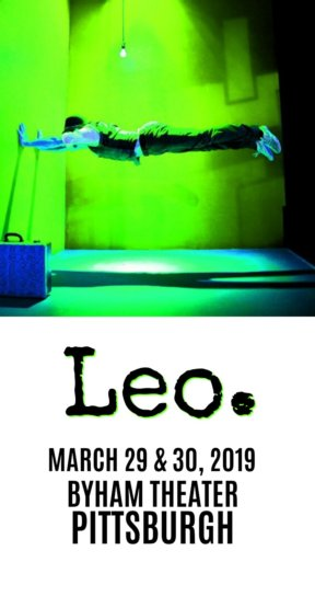 "stage lit in green empty of everything but a hanging lightbulb, a blue suitcase and a man apparently floating in a plank position, supported only by his hands pressing against the wall at a 90 degree angle. Underneath text reading, ""Leo. March 29 & 30, 2019, Byham Theater, Pittsburgh"""