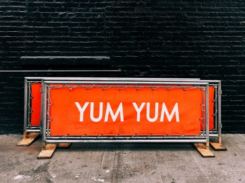 "orange banners sitting in an alley that read ""Yum Yum"" in white writing."