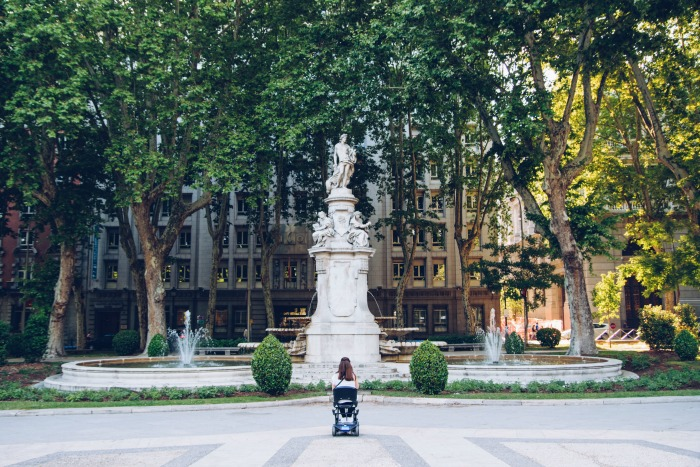 woman in a wheelchair in front of an imposing fountain with greco-roman statues i the middle. In an urban area with buildings in the background, but lots of mature trees surround the fountain.