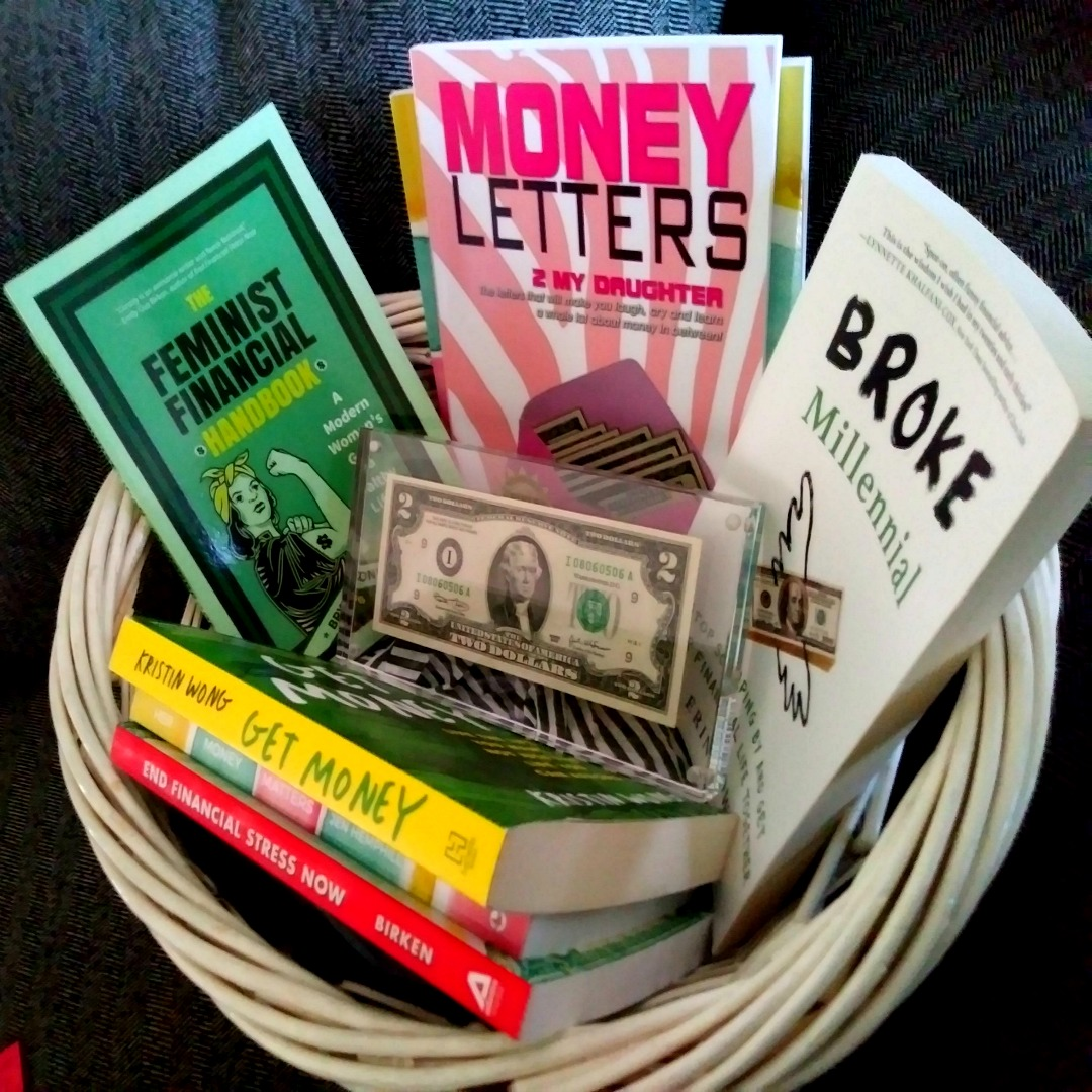 "Several books and a mounted $2 bill in a white basked with a grey background. Titles are: ""The Feminist Financial Handbook"" by Brynne Conroy, Money Letters 2 My Daughter by Jackie Cummings Koski, Broke Millennial by Erin Lowry, Get Money by Kristin Wong, Her Money Matters by Jen Hemphill and End Financial Stress Now by Emily Guy Birken."