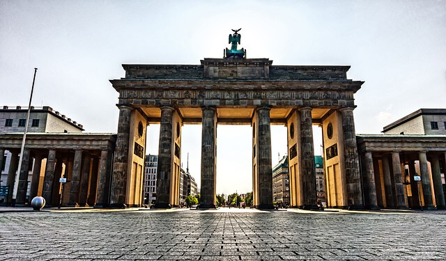 Large, pillared stone gate with sun shining through from the back. Located in Germany.