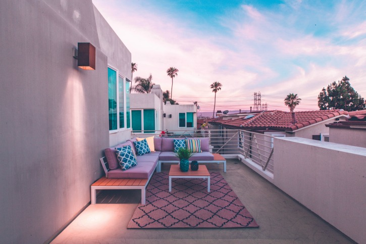 Outside deck with pink hues and blue pillows under a Califonian sky lined with other houses, palm trees and expansive white clouds in a blue sky.