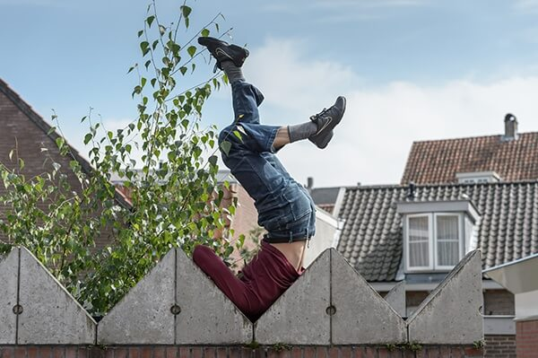 Man in maroon shirt, blue jeans and sneakers positioned upside down between the edges of a fence, balancing on his shoulder.