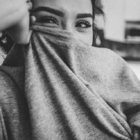 Black and white image of a girl pullingi a grey pajama tee over her face.