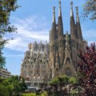 Sagrada Familia in Barcelona with a bright blue sky and a few wisps of clouds.