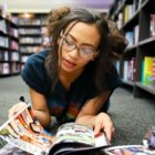 girl with glasses reading a comic book, lying down in between the shelves of the library