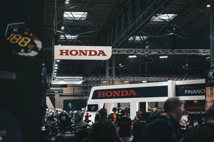 Many people milling around a crowded Honda booth at a trade show in a warehouse.