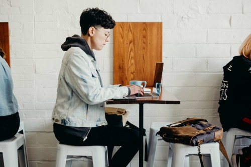 Individual sitting at at desk in a coffee shop working on a laptop.