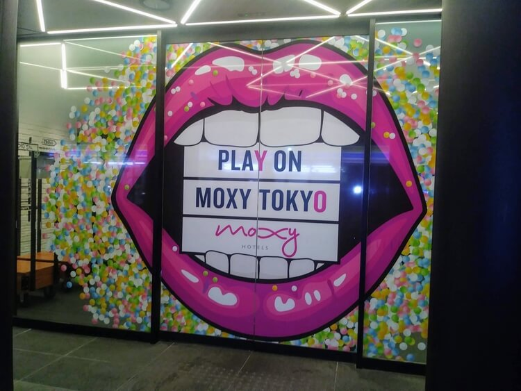 "Sliding door with woman's lips on it, between her teeth insider her mouth it says ""Play on Moxy Tokyo moxy"""