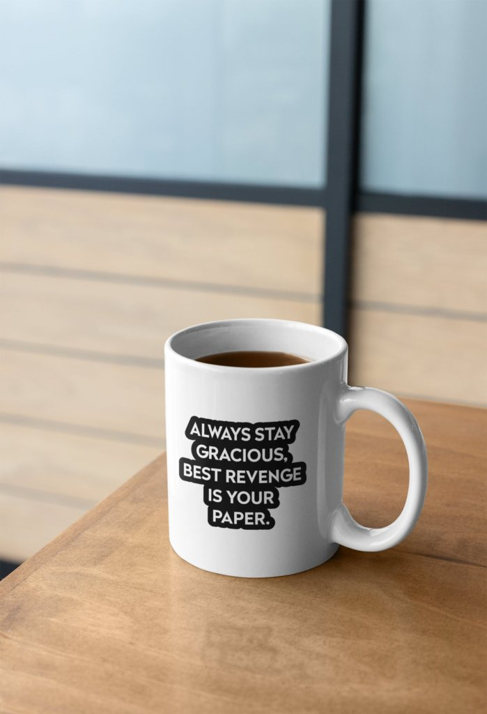 mug on table against neutral blue and brown background. mug full of coffee and says 'always be gracious, best revenge is your paper'