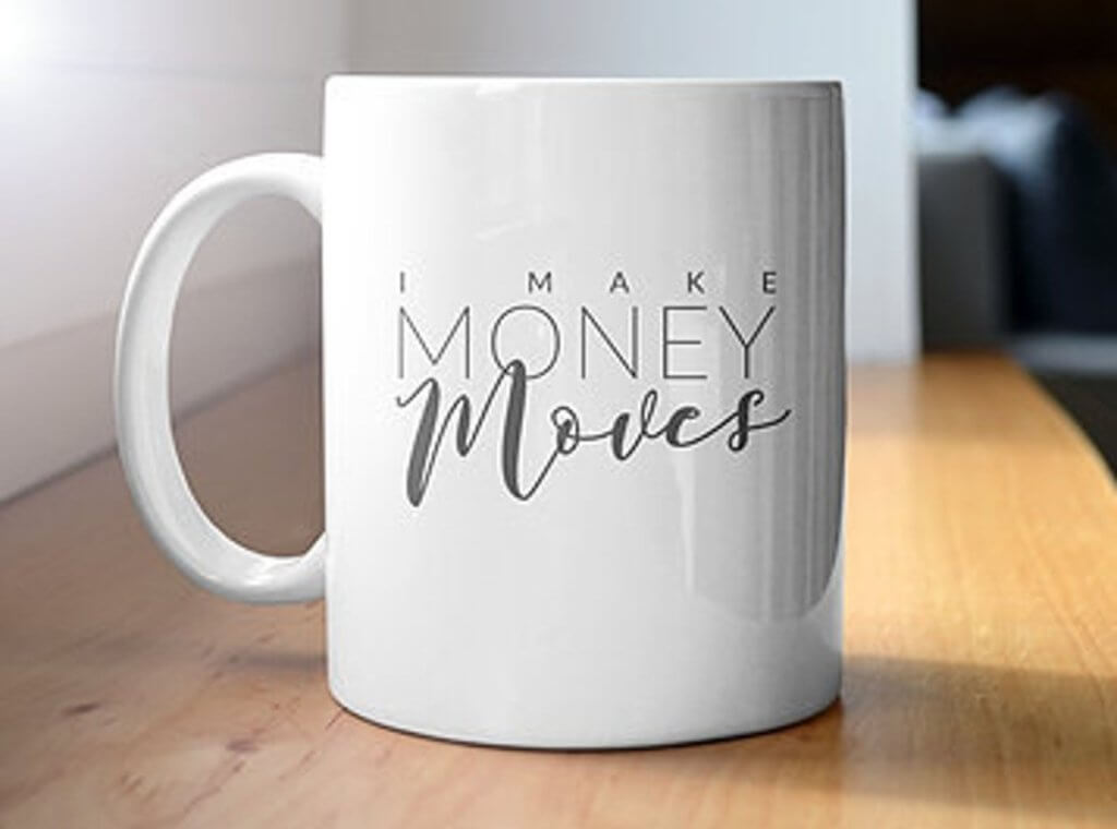 "Coffee mug sitting on a wooden floor with the words ""i make money moves"" printed on it."