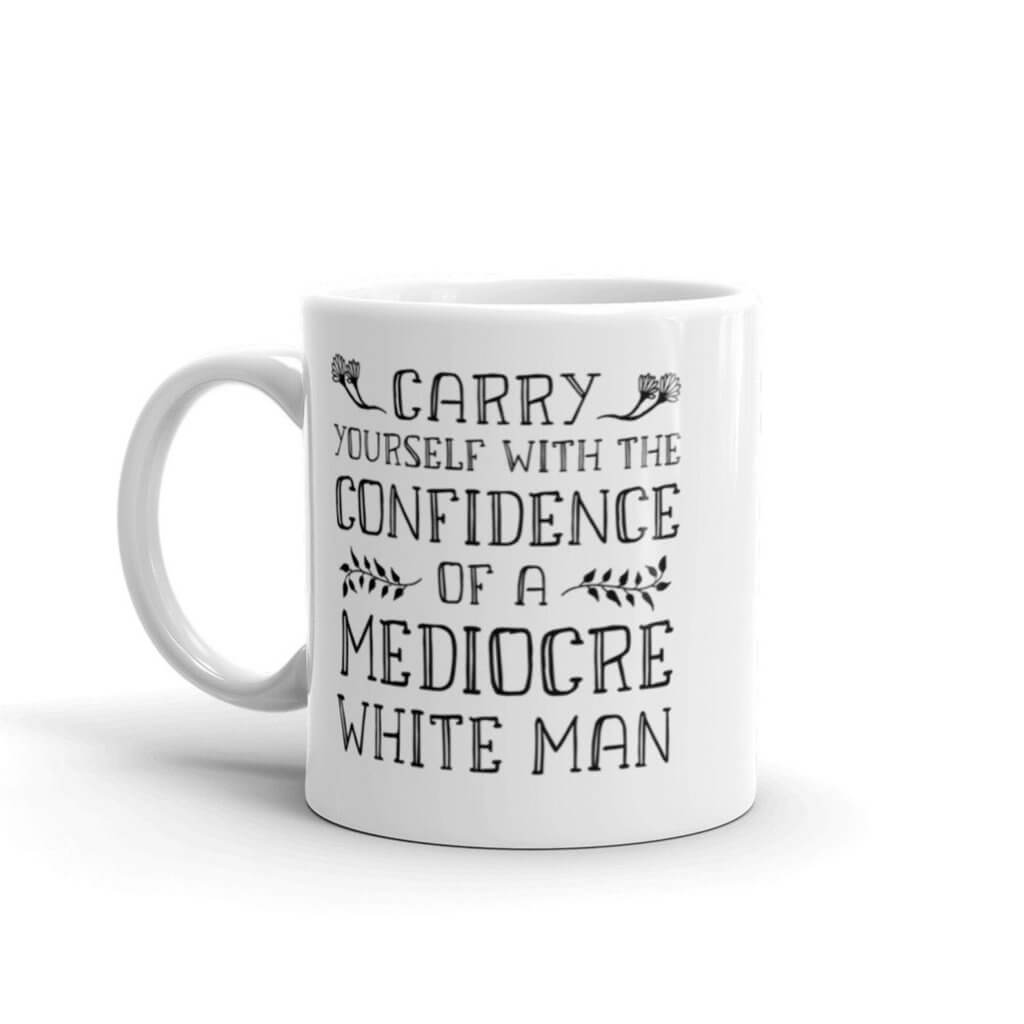 """white coffee mug with black words printed on it looking like cross stitch: """"Carry yourself with the confidence of a mediocre white man"""