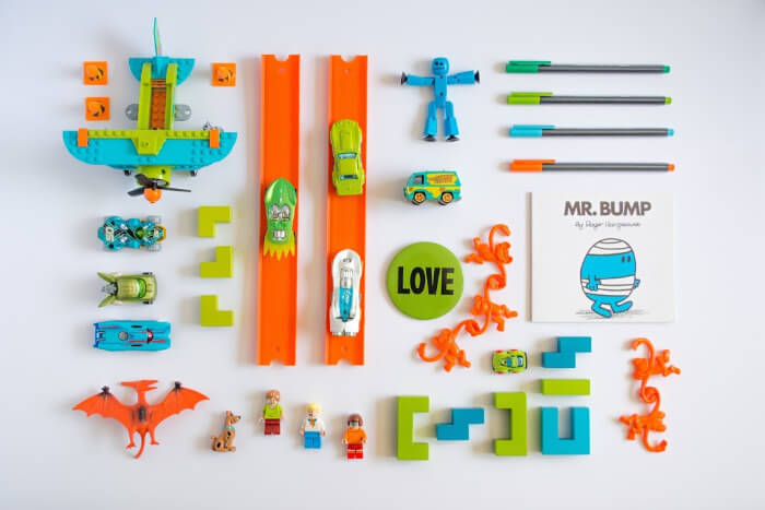 a bunch of toys lined up with a color scheme of green, orange blue and white.