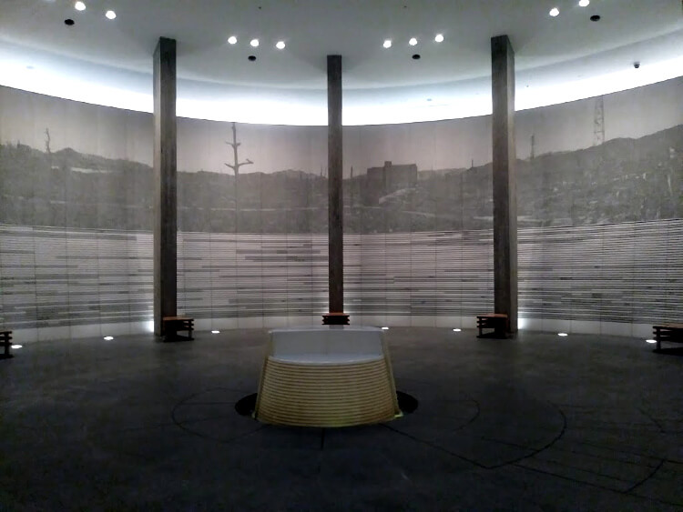 a room with circular walls depicting ruined buildings, rubble and dead trees after the bombing in hiroshima