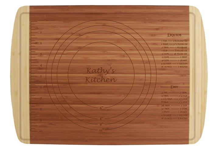 "Bamboo cutting board, light on the outside darker wood on the inside. Cooking coversions etched into the bamboo, along with the radius for different pie crust or bread dough radiuses. Inside the circles is etched ""Kathy's Kitchen"" -- a personalization which can be customized to your name."
