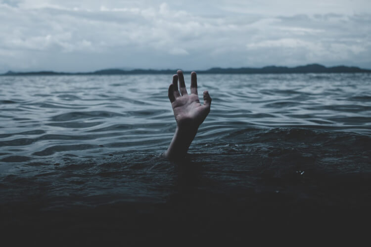 hand sticking up from dark water, indicating drowning.