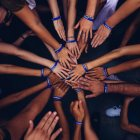 Many hands of varying skin tones putting their hand in the middle of a circle.