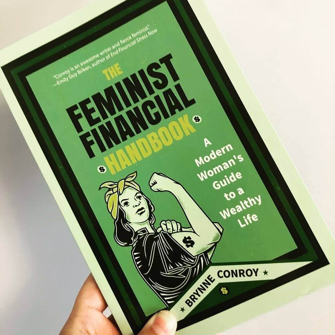 Woman holding a copy of The Feminist Financial Handbook on a white background.