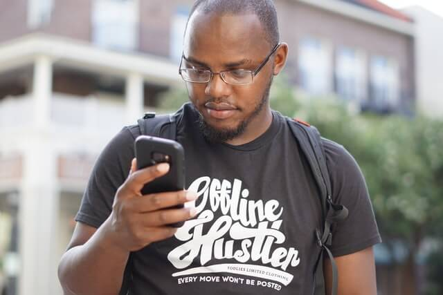 """Man looking at phone. Shirt says """"Offline Hustler Every Move Won't Be Posted Foolies Limited Clothing"""""""