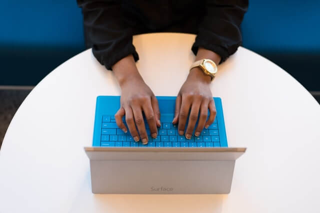 Black woman wearing black sweater typing at a blue keyboard