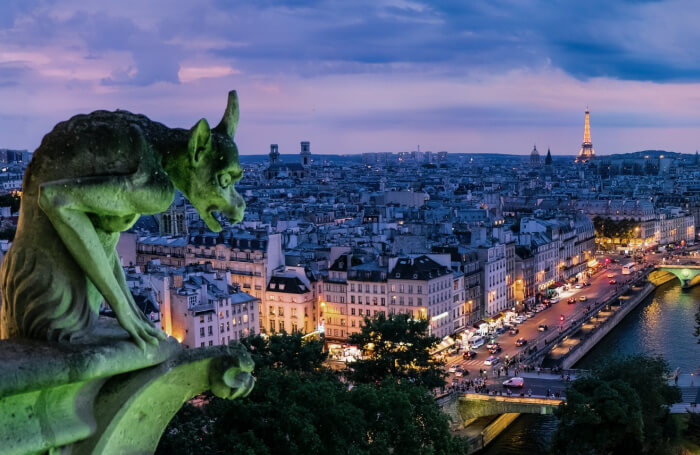 Gargoyle lit in green looking over Paris at twilight to the Eiffel Tower.