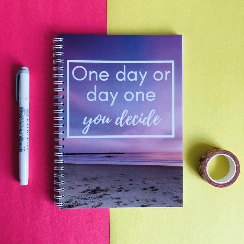 """Journal, pen and washi tape on a pink and yellow background. Notebook read, """"One day or day one you decide"""" on the front."""
