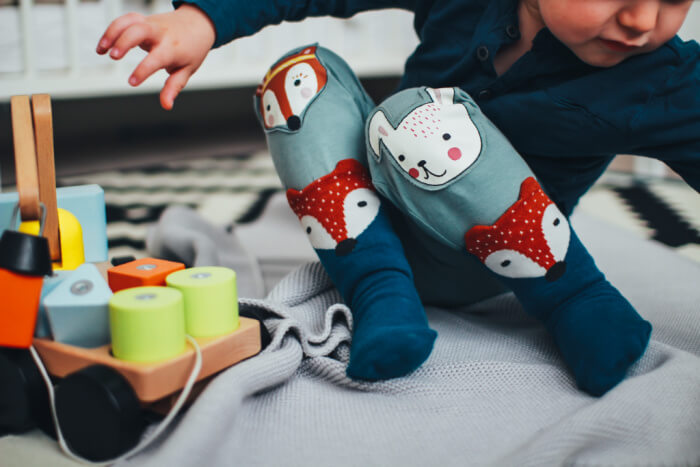 Child wearing tights with woodland animals on them playing with a stacking wagon toy.