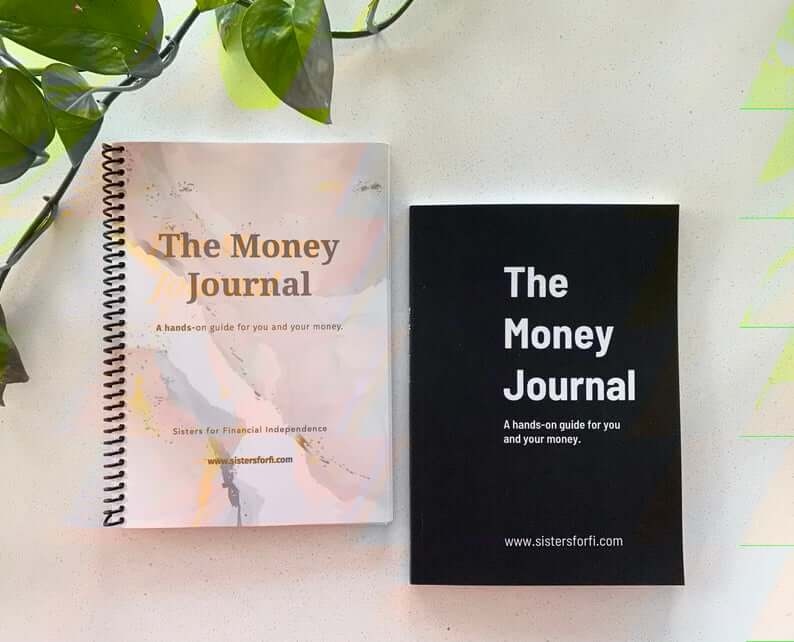 Two copies of 'The Money Journal', one spiral, a darker cover is bound. Sitting on a white background next to a green plant.