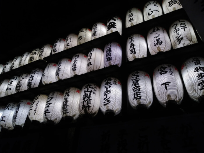 Lit white Japanese lamps with black lettering.