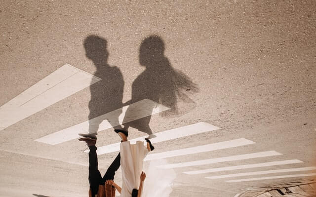 The shadow sillohettes of a girl and boy crossing a crosswalk. The way the photo is shot, it lookslike the girl's and boy's bodies are upside down while the shadow are upright.