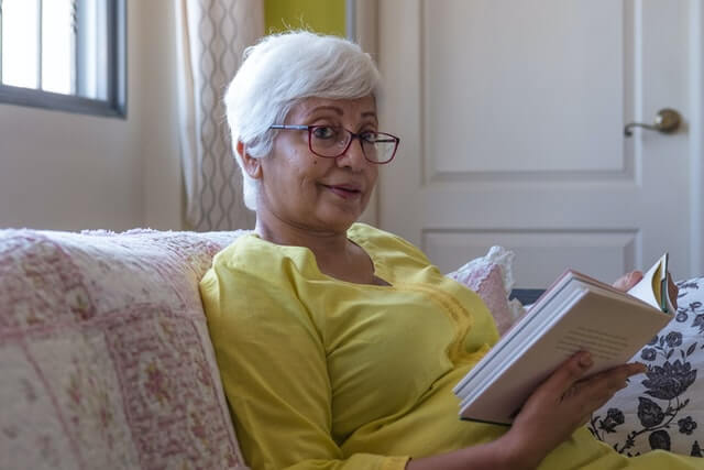 Woman in a yellow shirt with glasses sitting on a couch reading a book.