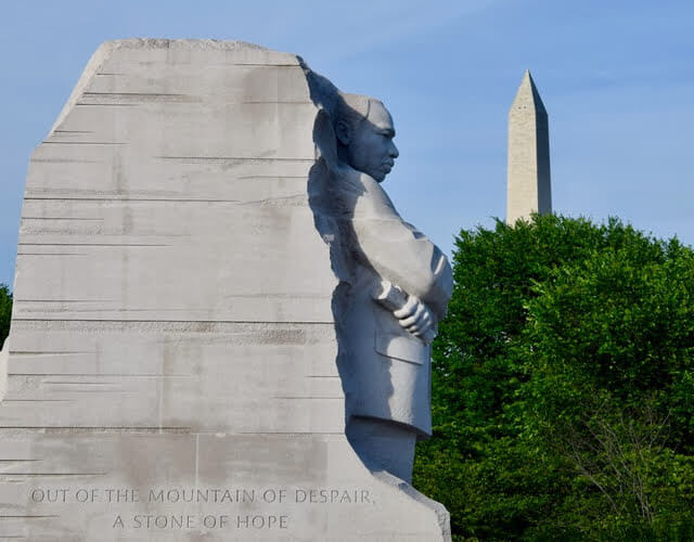 MLK Monument in DC. A mountainous bulk of stone. On the front it reads, 'Out of the mountain of despair a stone of hope.' MLK's profile is carved into the side of the rock. From this angle, it looks like he is looking directly at the Washington Monument.