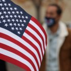 US flag in foreground, two masked people walking in the background out of focus.