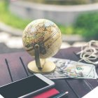 Small globe sitting on a wooden table with American cash, a phone, pen and paper and earphones.