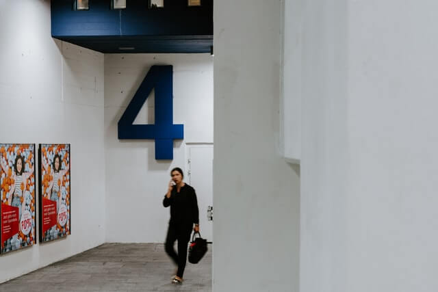 A woman with a blurry face walking through a public transit station. Blue platform number is shown in the background: 4.
