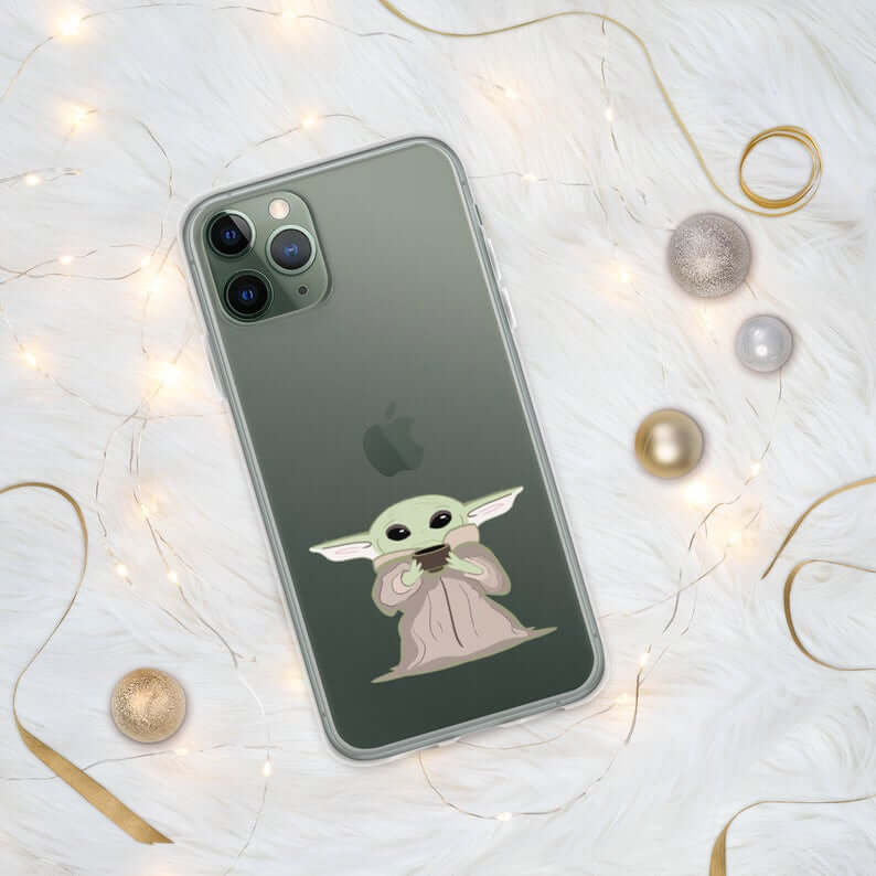clear iphone case on black phone. baby yoda is printed at the bottom of the case drinking out of a cup