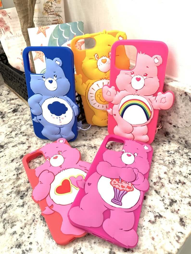 5 different iphone cases with 3d care bears on the back. Patterns are top row: grumpy bear, funshine bear, cheer bear. bottom row: Love-a-lot bear and share bear.