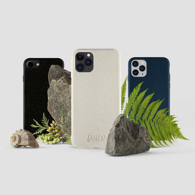 3 iphones in simple black, white and blue cases with the word 'wild' etched at the bottom. Rocks and ferns are also in the background for decoration
