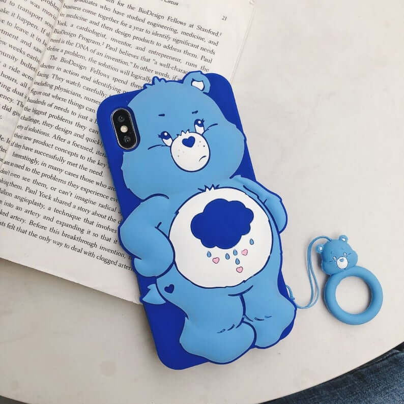 Blue iphone case with grumpy bear on back. Sitting on an open book but it's not clear what the book is about.
