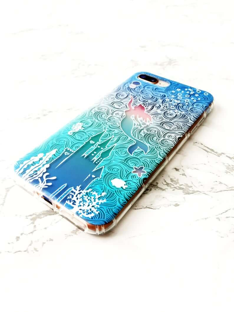 blue and green iphone case with a white outline of a castle, ariel from the little mermaid and swirls of ocean water