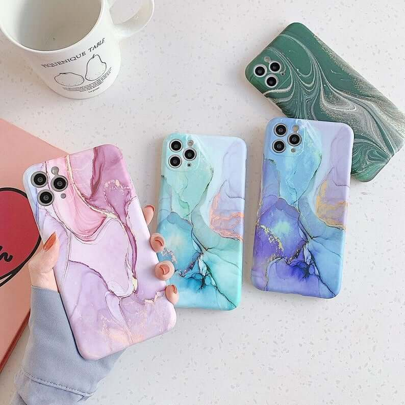 woman holding a pink, marbled iphone case with a vein of glitter. 3 iphones with similar patterned cases are lying on the table only the marble's primary clors are blue, purple and dark green respectively.