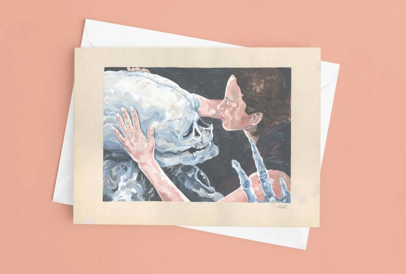 greeting card with painting of a woman tenderly holding the skull of an alien skeleton that appears to be alive between her hands.