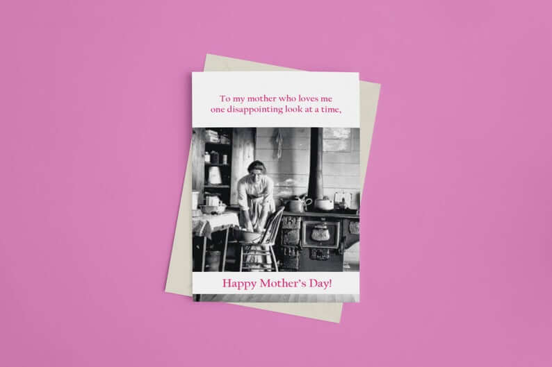"Greeting card with a picture of a woman kneading bread in an 1800s kitchen. Above, text reads ""To my mother who loves me, one disappointing look at a time,"" Below, text reads ""Happy Mother's Day!"""