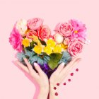 Woman's hands holding up a bouquet of flowers shaped like a heart, mostly matching the colors of the rainbow. Pink background. Ladybugs crawling up woman's right wrist and hand.