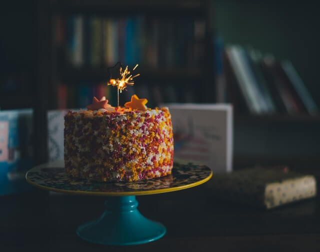 birthday cake with star sprinkles sitting in a library with a sparkler candle