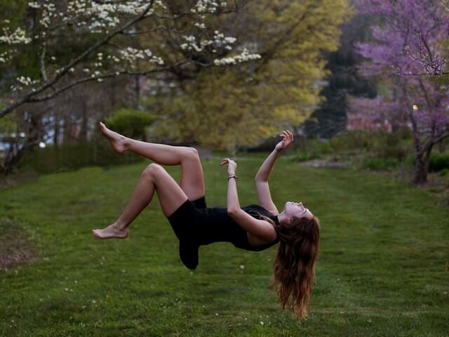 A photo where it looks like a woman is falling to the ground on her back from the top of some springtime trees